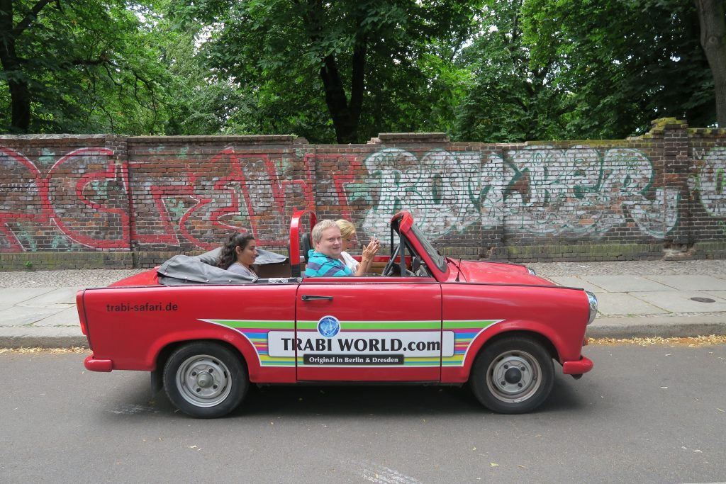En röd cabbad Trabant tog oss runt i Berlin. Daniela i baksätet och ledsagaren Eva vid ratten.